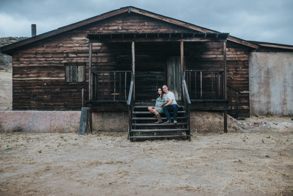 Color image of belly session at the Ranch Melody. Expecting woman and her partner sit on the steps of an old wooden cabin that appears to have once be burned.