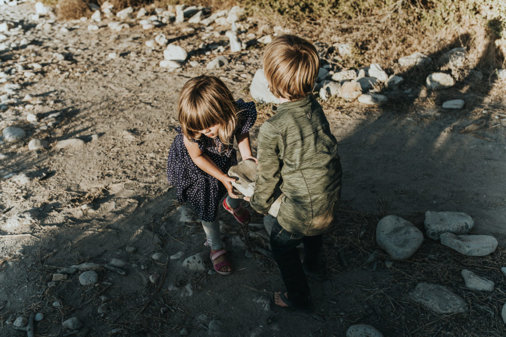 Color image twin brother and sister playing with rocks at the beach, captured by ArtShaped Photography in Rancho Palos Verdes,Los Angeles