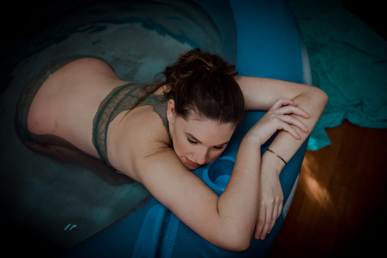 Color image of woman resting on the edge of a birth tub. She is wearing a torquise top bralette and has her head turned on the side. Image courtesy of Los Angeles Birth Photographer Diana Hinek for ArtShped Photograohy and Birth Services.