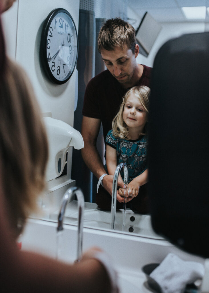 Color image of man washing the hands of a toddler in front of a mirror. A clock is visible on the wall next to them. Child is looking at the mirror. Image by Los Angeles birth photographer Diana Hinek for #dearbirth