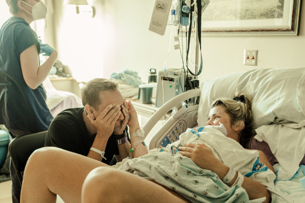Color image of birth scene. Mom caresses dad's face while holding her newborn on her chest in a hospital bed. Dad covers his eyes with his hands. Nurse wearing a mask walks in the back. Image captured by back up birth photographer April Trettel for Los Angeles birth photographer Diana Hinek of DearBirth.