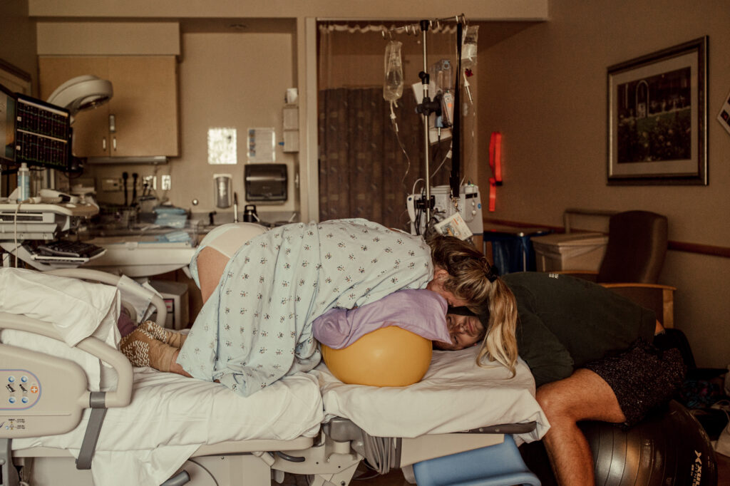 Color image of mother laboring hands and knees on a peanut ball in a hospital bed. Partner is resting below her with his head on the bed facing the camera. Image by back up artist April Trettel for birth photography services #dearbirth in Los Angeles California. What is a back up in birth?